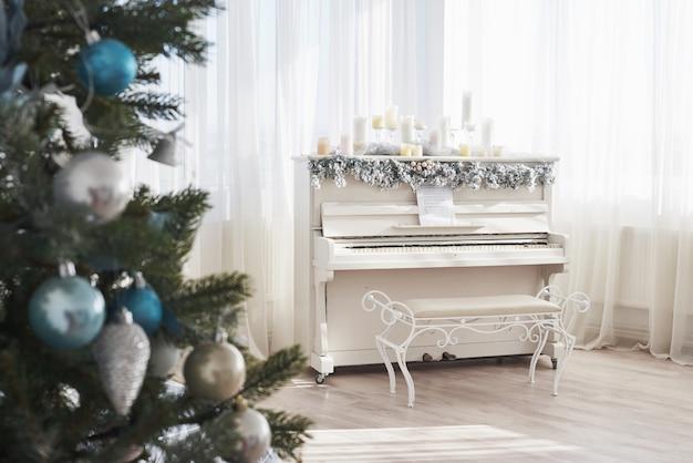 Décoration Du Nouvel An. Sapin De Noël Près D'un Piano Blanc à La Fenêtre Photo Premium