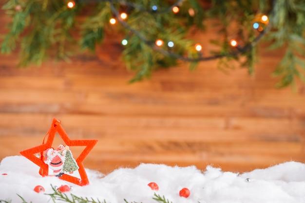 Décoration étoile de noël dans la neige avec guirlande Photo gratuit