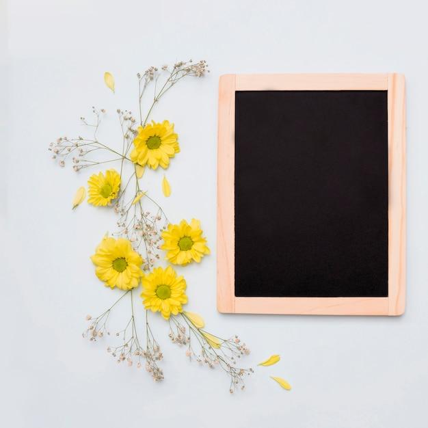 Décoration de fleur jaune près de l'ardoise vierge en bois sur fond blanc Photo gratuit