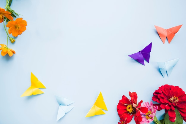 Décoration avec des fleurs de calendula et des papillons en papier origami sur fond bleu Photo gratuit