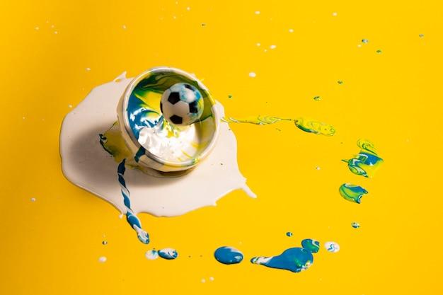 Décoration grand angle avec peinture jaune et ballon de foot Photo gratuit