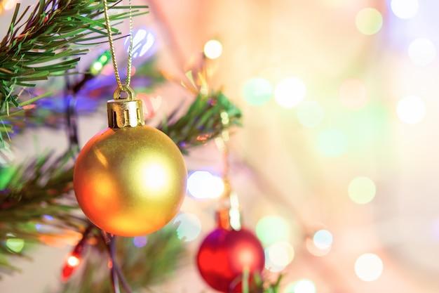 Décoration De Noël. Accrocher Des Boules D'or Sur Des Branches De Pin Guirlande D'arbres De Noël Et Ornements Sur Fond De Bokeh Abstrait Avec Fond Photo Premium