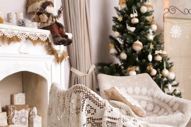 Décoration de noël aux couleurs beiges naturelles, cheminée artificielle avec cadeaux, deux fauteuils et arbres de noël décorés. Photo Premium