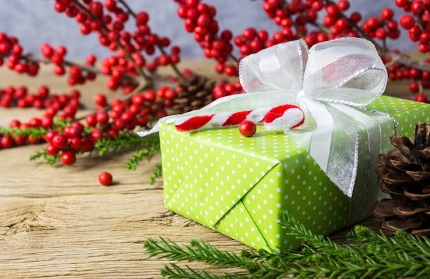 Décoration de noël de boîte de cadeau vert et hiver rouge sur vieux bois Photo Premium