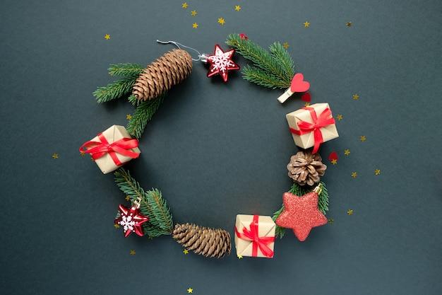 Décoration de noël avec des branches, des étoiles, des boîtes-cadeaux et des pommes de pin, cadre arrondi sur fond noir Photo Premium