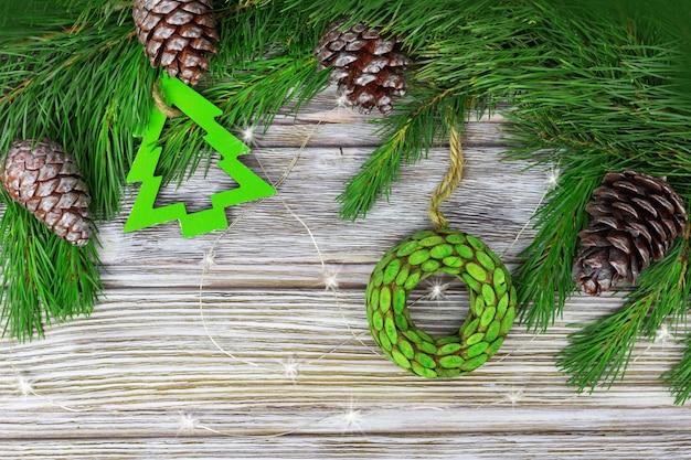 Décoration De Noël Sur Des Branches De Pin. Cônes Naturels Et Jouets En Bois Sur Fond De Bois Grunge. Vue De Dessus Et Espace De Copie. Photo Premium