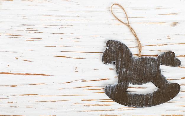 Décoration de noël, un cheval de bois sur une vieille table blanche. nouvel an. Photo Premium