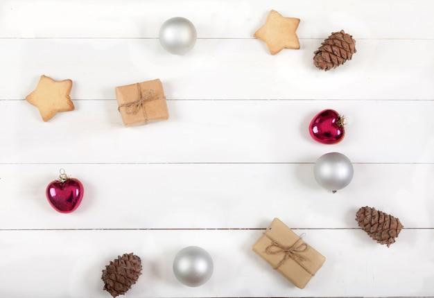 Décoration De Noël Et Du Nouvel An De Boules, Cônes De Cèdre, Biscuits, Cadeaux Et Coeurs Sur Une Surface En Bois Blanche Photo Premium