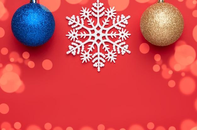 Décoration De Noël Sur Fond Rouge Représentant Deux Boules De Noël Et Un Grand Flocon De Neige Au Centre Photo Premium