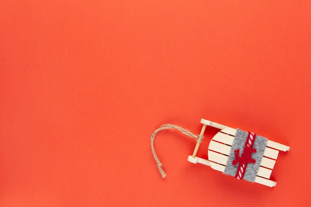 Décoration De Noël, Jouet D'arbre, Traîneau En Bois Avec Cerf Sur Fond Rouge Avec Fond. Festif, Nouvel An Photo Premium