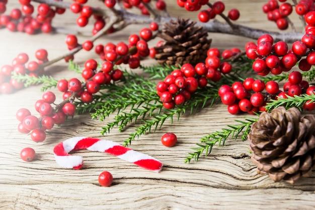 Décoration de noël de pomme de pin et d'hiver rouge sur vieux bois Photo Premium