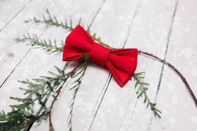 Décoration de noeud papillon de noël avec de la neige sur un fond en bois blanc. Photo Premium
