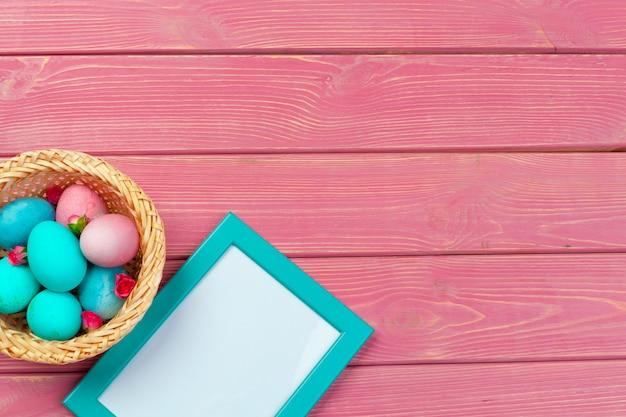 Décoration de pâques avec des oeufs et un cadre vide. vue de dessus Photo Premium