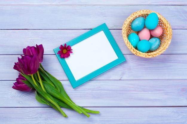 Décoration de pâques avec des tulipes, des œufs et un cadre vide. vue de dessus Photo Premium