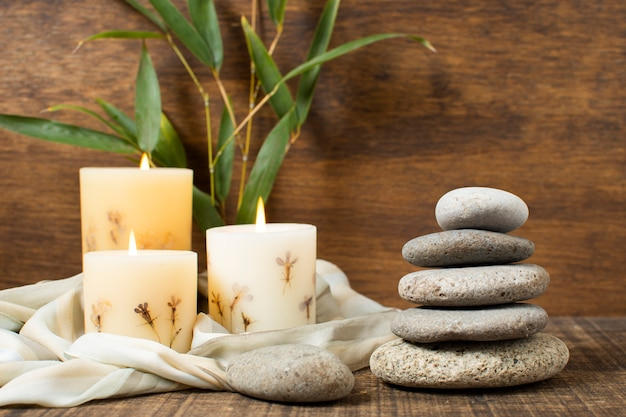Décoration avec des pierres de spa et des bougies allumées Photo gratuit