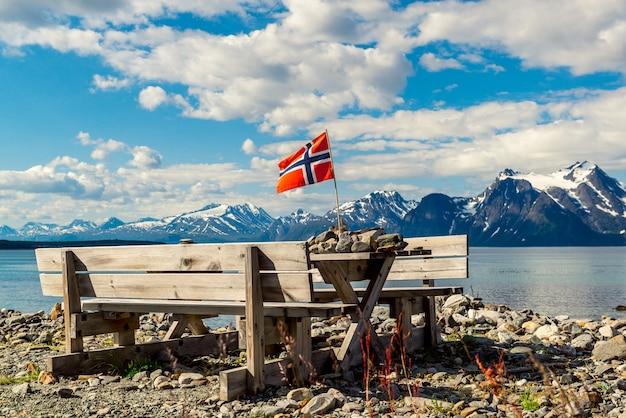 Décoration de table en bois et drapeau norvégien sur la rive du fjord du lac. Photo Premium