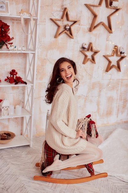 Décoration de vacances d'hiver. couleurs chaudes. charmante femme brune en pull beige Photo gratuit
