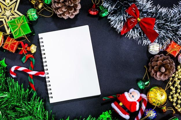 Décorations de noël avec carnet vide et un crayon sur fond de papier noir Photo Premium