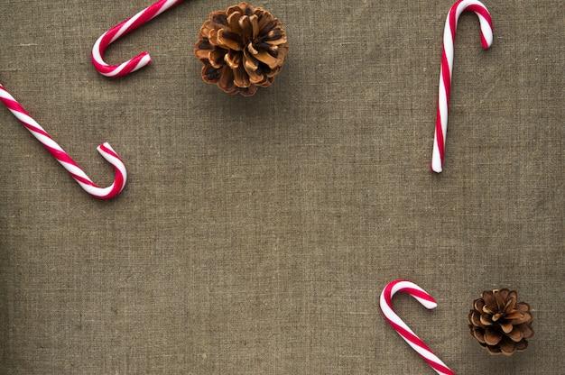 Décorations de noël: vue de dessus des cannes de bonbon et des cônes sur fond de toile de lin avec espace libre Photo Premium