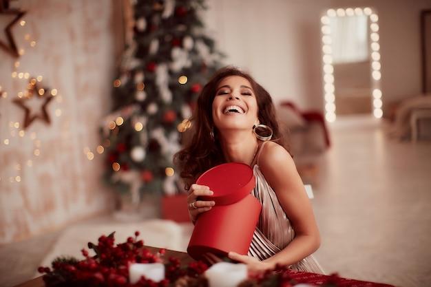 Décorations de vacances d'hiver. couleurs chaudes. charmante femme brune en robe beige Photo gratuit