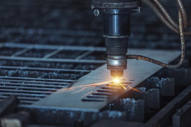 Découpe laser de métaux cnc, technologie industrielle moderne. faible profondeur de champ. Photo Premium