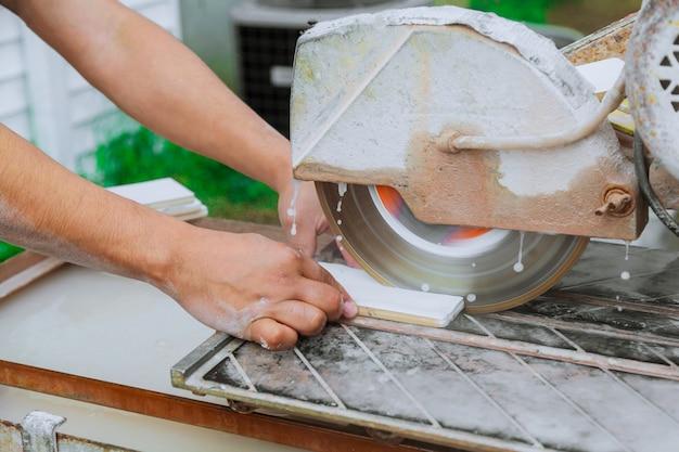 Découpe manuelle de carreaux de céramique sur une machine spéciale pour la découpe de carreaux. Photo Premium