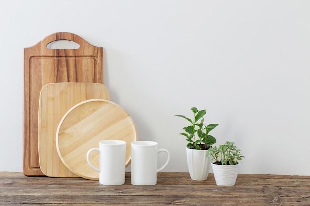 Découper Des Planches En Bois, Des Tasses Blanches Et Des Plantes Vertes Sur Une étagère En Bois Photo Premium