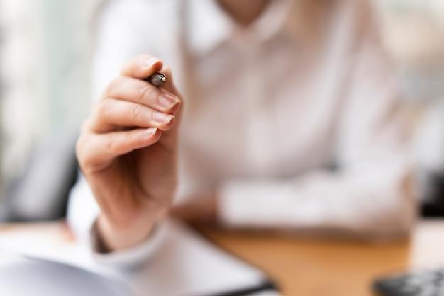 Défocalisé femme pointant le stylo bouchent Photo gratuit