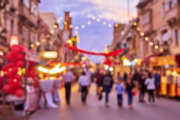 Défocalisé foule de gens pendant la foire de noël, une rue de la vieille ville Photo Premium