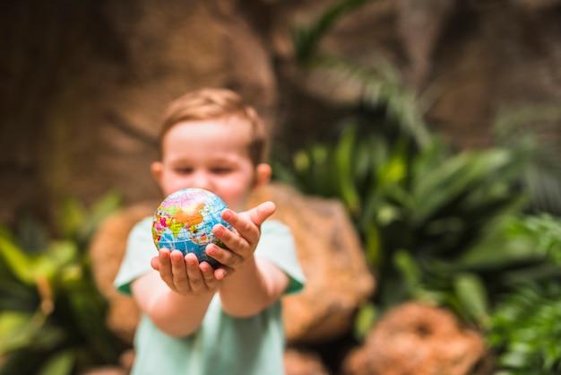 Défocalisé garçon tenant la boule dans la main Photo gratuit