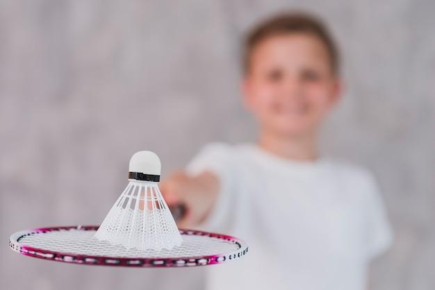 Défocalisé garçon tenant un volant sur la raquette contre le mur gris Photo gratuit