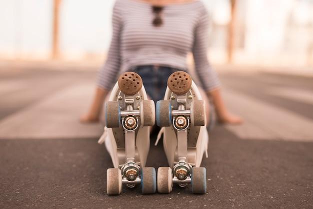 Défocalisé jeune femme assise sur le sol avec des patins à roulettes sur ses pieds Photo gratuit
