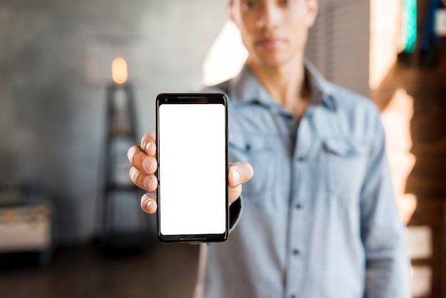 Défocalisé jeune homme montrant un téléphone mobile à écran blanc Photo gratuit