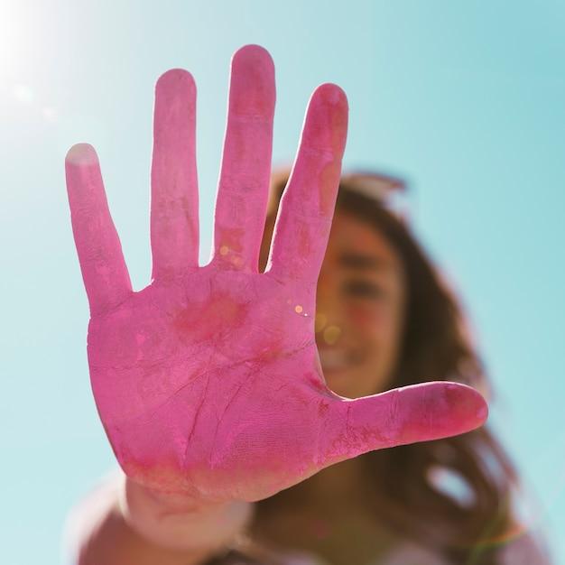 Défocalisée jeune femme montrant sa main peinte couleur rose holi au soleil sur ciel bleu Photo gratuit