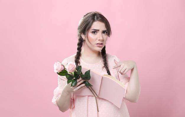 Dégoûté Femme Tenant Des Roses Et Pointant Sur Le Livre Photo gratuit