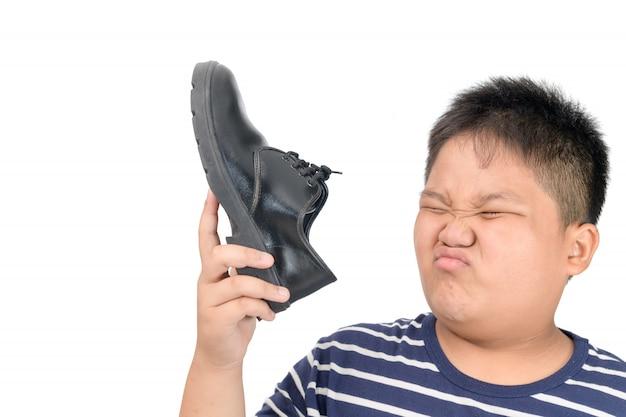 Dégoûté garçon tenant une paire de chaussures en cuir malodorantes Photo Premium