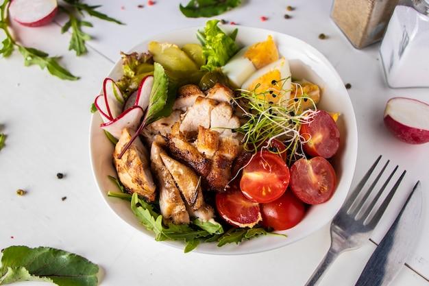 Déjeuner-bol sain avec du poulet cuit au four, du quinoa, des tomates cerises, des radis, des œufs, des cornichons concombre, des micro-verts et de la roquette Photo Premium