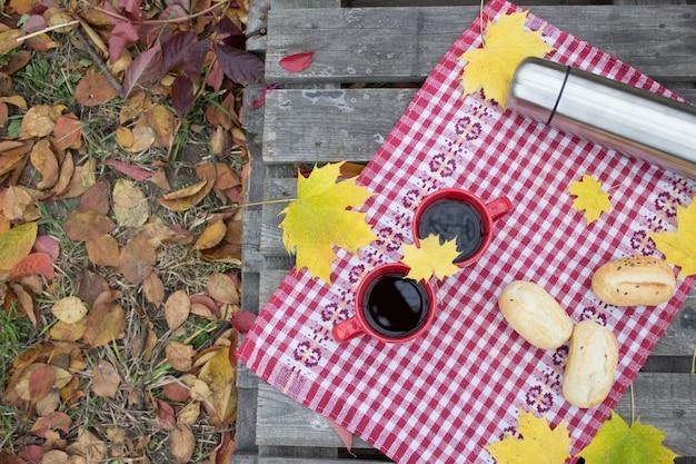Déjeuner dans la nature, romance d'automne. deux tasses rouges et un thermos avec une boisson chaude Photo Premium