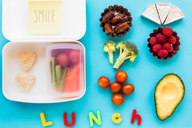 Déjeuner écrit près de la nourriture et de la boîte à lunch Photo gratuit
