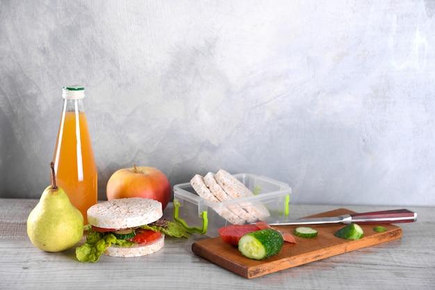 Déjeuner Pour Votre Enfant à L'école, Boîte Avec Un Sandwich Santé, Une Salade De Fruits Et Du Jus De Pomme Dans Le Biberon Photo Premium