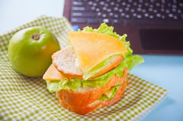 Déjeuner avec un sandwich et une pomme verte et un ordinateur portable sur la table. Photo Premium