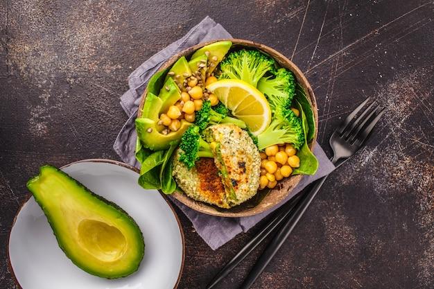 Déjeuner végétalien dans un bol en noix de coco: hamburgers verts avec salade et pois chiches. Photo Premium