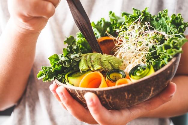 Déjeuner végétalien sain dans un bol de noix de coco. un enfant mange un bol de bouddha. Photo Premium