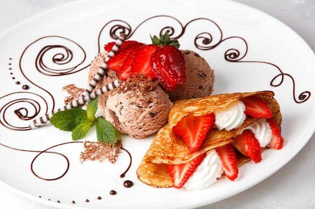 Délicieuse crêpe à la fraise fraîchement cuite avec de la glace au chocolat Photo Premium