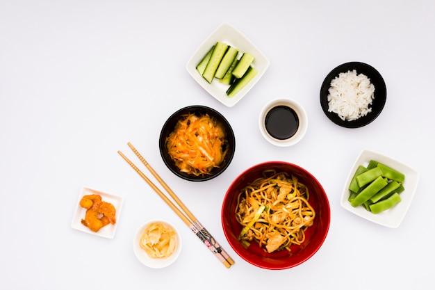 Délicieuse cuisine asiatique avec des ingrédients disposés sur un fond blanc Photo gratuit