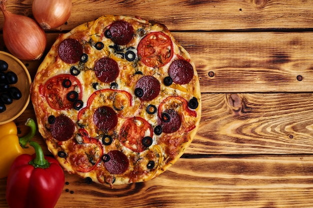 Délicieuse Pizza Au Salami, Olives, Poivrons Rouges Et Tomates Sur Bois. Rustique. Aliments. Vue De Dessus. Copiez L'espace. Photo Premium