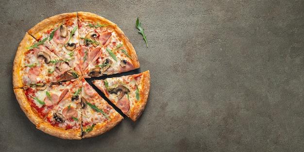 Délicieuse pizza chaude dans une boîte avec du jambon. Photo Premium
