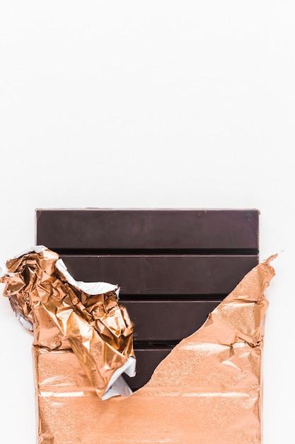 Délicieuse tablette de chocolat enveloppée dans une feuille d'or sur fond blanc Photo gratuit
