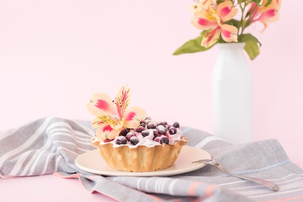 Délicieuse tarte aux myrtilles et alstroemeria fleurie sur une plaque en céramique sur fond rose Photo gratuit