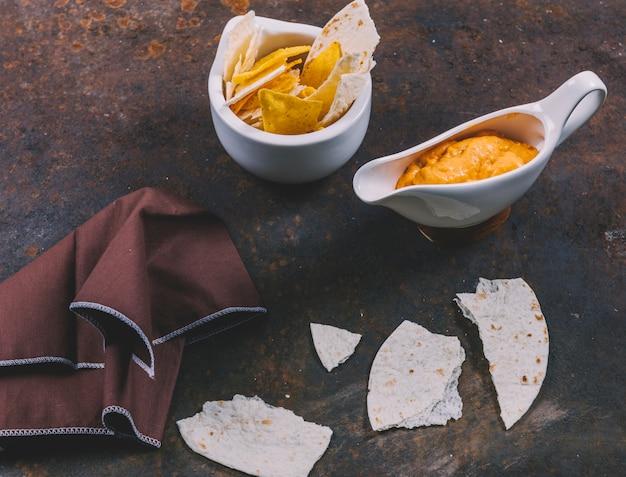Délicieuse tortilla mexicaine avec nachos dans un bol avec trempette au fromage et serviette de table sur fond rouillé Photo gratuit